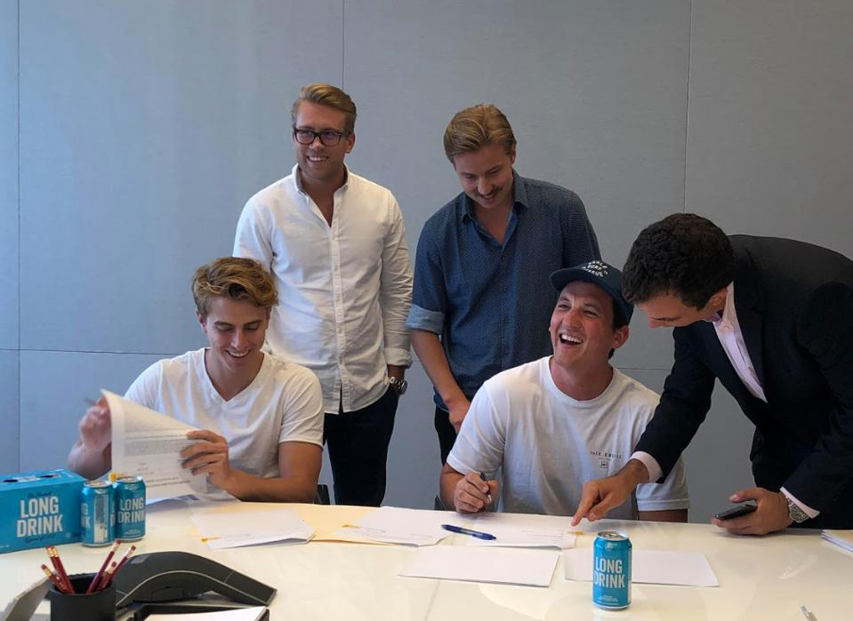 Miles Teller, star of Top Gun: Maverick, signs paperwork earlier this summer.