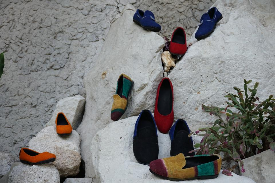 Hand-dyed shoes placed on white rocks.