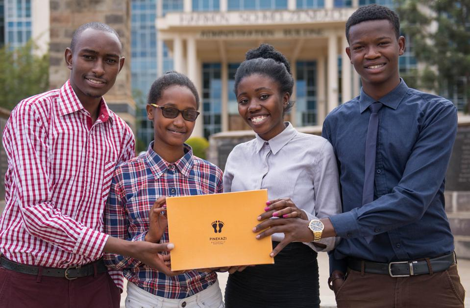 Four young Kenyan students hold a shoebox.