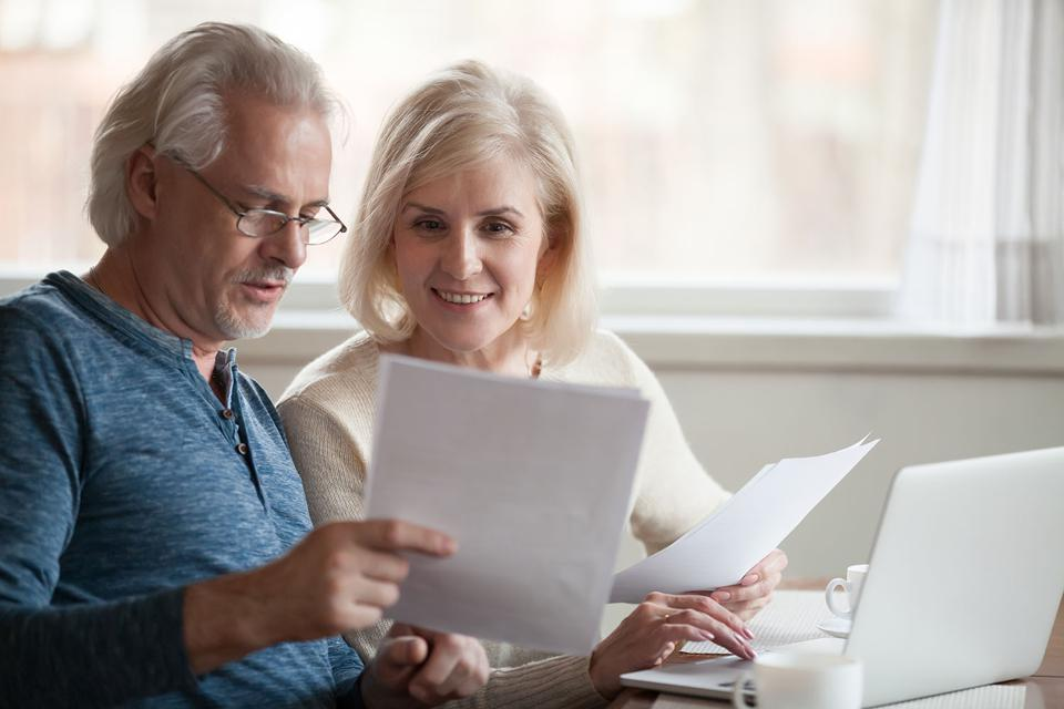 Smiling older couple reading statements for their retirement accounts