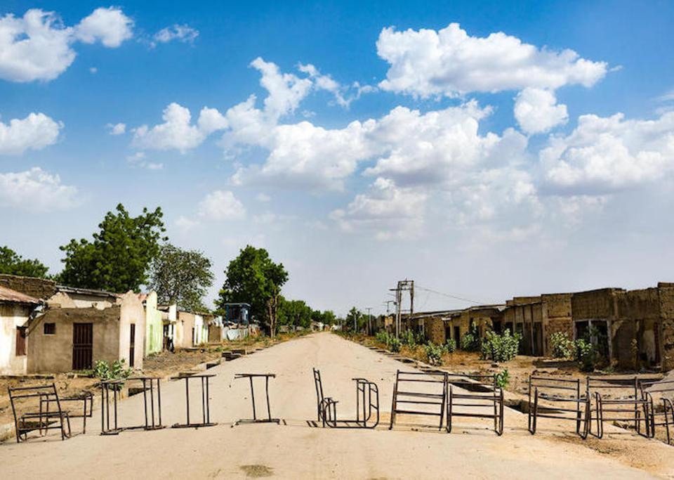 Güvensizlikten kaçan aileler tarafından terk edilmiş evlerin, dükkanların ve okulların boş durduğu kuzeydoğu Nijerya'daki Banki kasabasının eteklerinde, yolun karşısında eski masalar sıralanıyor.