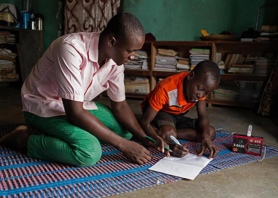 In Dori, Burkina Faso, radio school facilitator Abdoulaye, 23, helps 14-year-old Hussaini through lessons broadcast as part of the UNICEF-supported Radio Education in Emergencies program.0