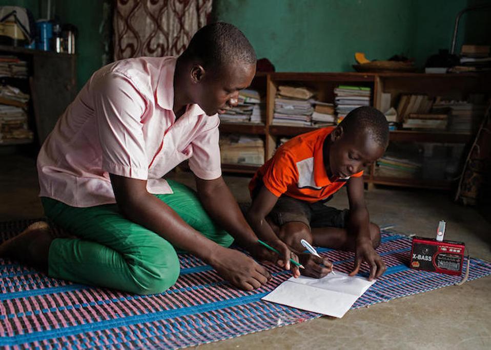 Sa Dori, Burkina Faso, ang facilitator ng paaralan sa radyo na si Abdoulaye, 23, ay tumutulong sa 14-taong-gulang na si Hussaini sa pamamagitan ng mga aralin na broadcast bilang bahagi ng programa ng Edukasyon sa suportang Radio sa UNICEF na sinusuportahan