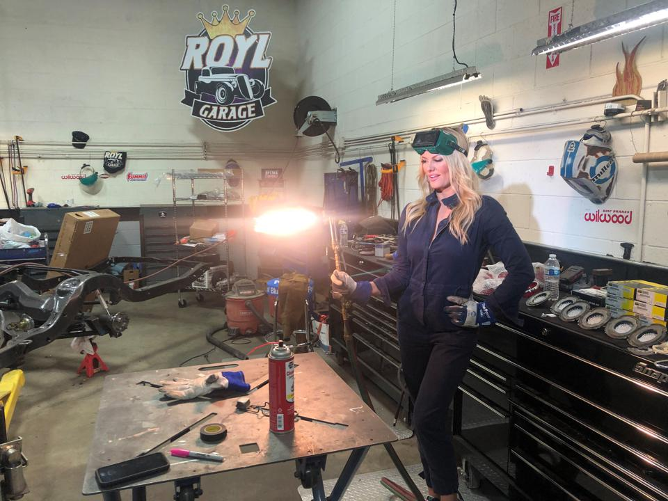 """Courtney Hansen, co-host and executive producer, filming on set, fixing up a car on her show 'The Ride That Got Away'""""."""