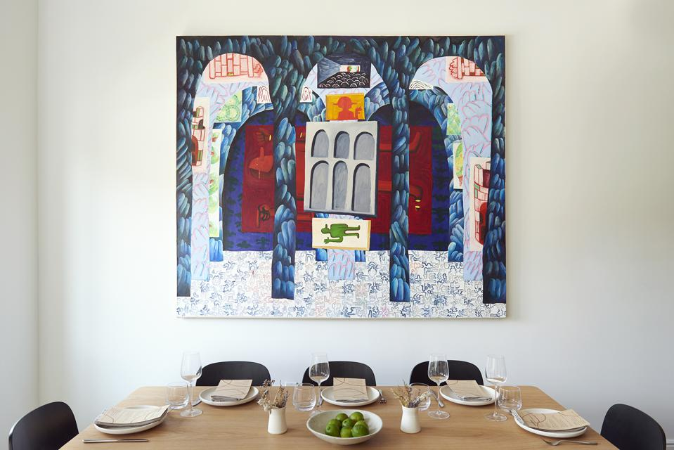 A kitchen table with a colorful painting behind it.