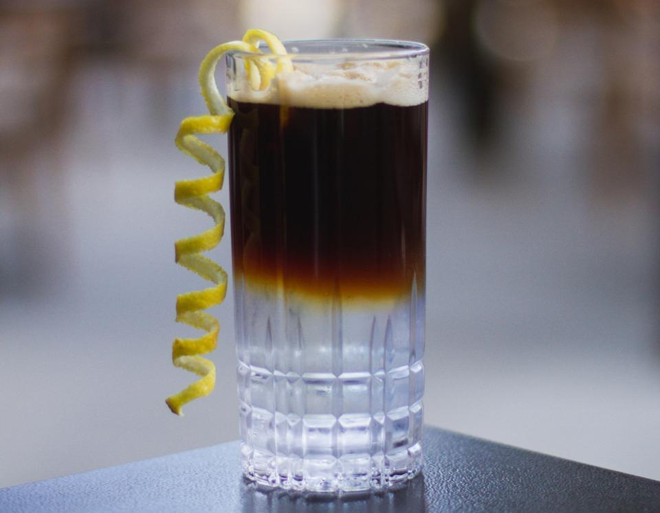 Coffee-based mocktail in a tall glass with lemon peel garnish.