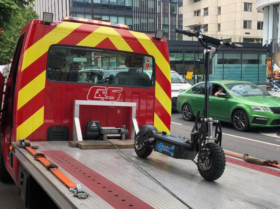 A single electric scooter being confiscated by police in London.