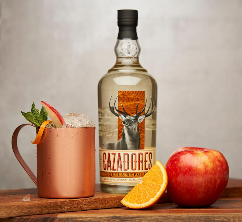 Apple cider cocktail in a copper mug, resting next to a tequila bottle, apple and orange.