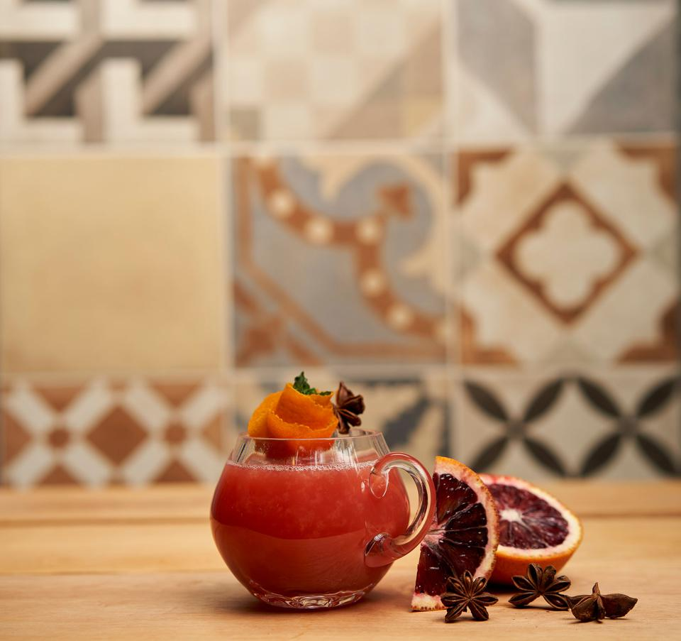 A garnet-hued hot toddy in a glass mug on a table with blood orange slices and star anise.