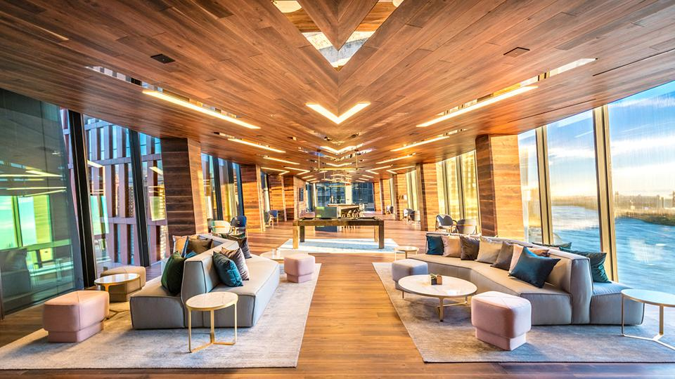 A wood paneled lounge with a view of the East River.