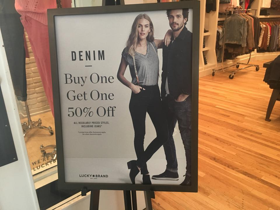 A photo of a sales promotion sales for Lucky Brand jeans featuring a female and a male model.