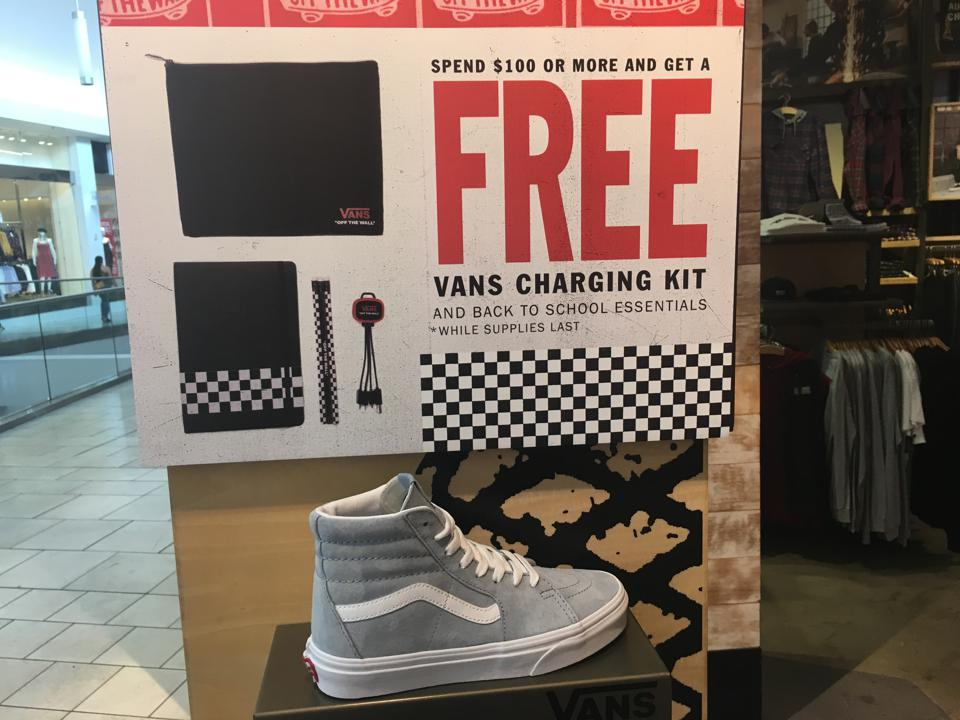 A display at a Van's store showing a grey sneaker and a sign advertising a free charging kit with purchase.