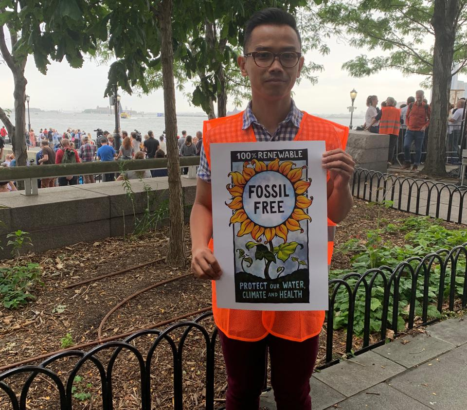 Organizer holding sign reading ″fossil free: protect our water climate and heath″