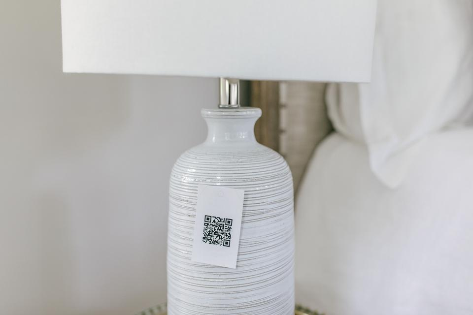 A white ceramic lamp with a QR code attached.