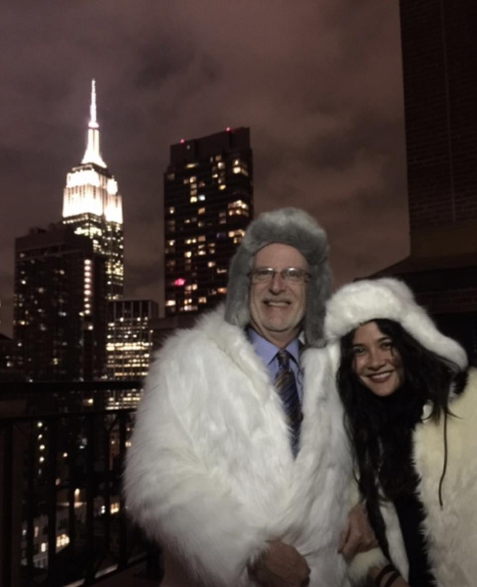 A man and woman in white faux fur coats stand on a terrace with the Empire State Building