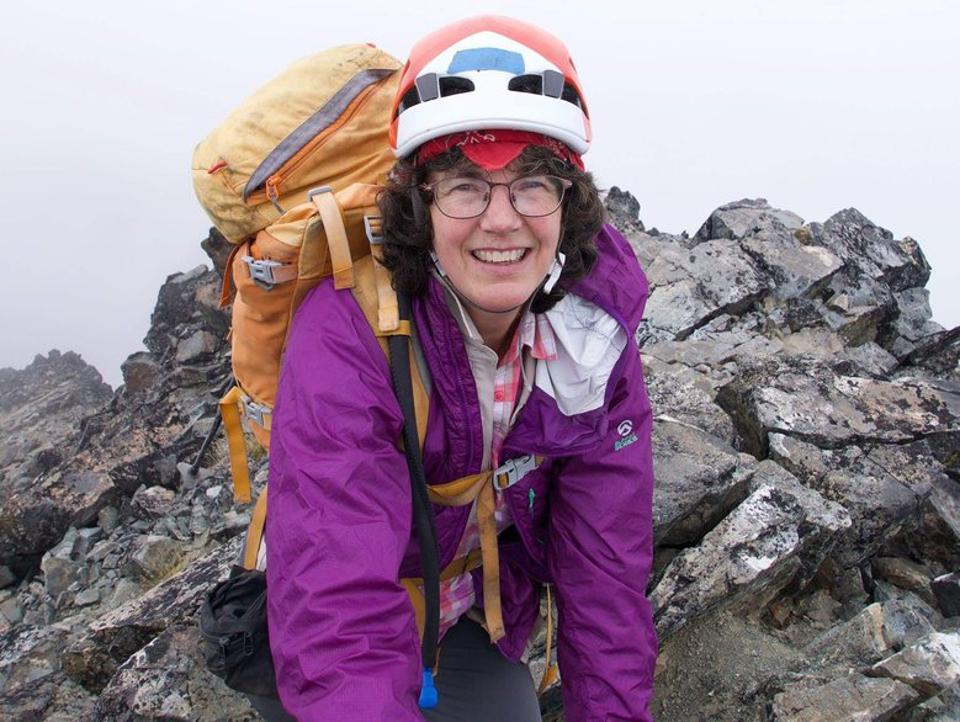 Color photo of Ann Nelson, in a purple jacket and yellow backpack, with a rock outcrop in the background.