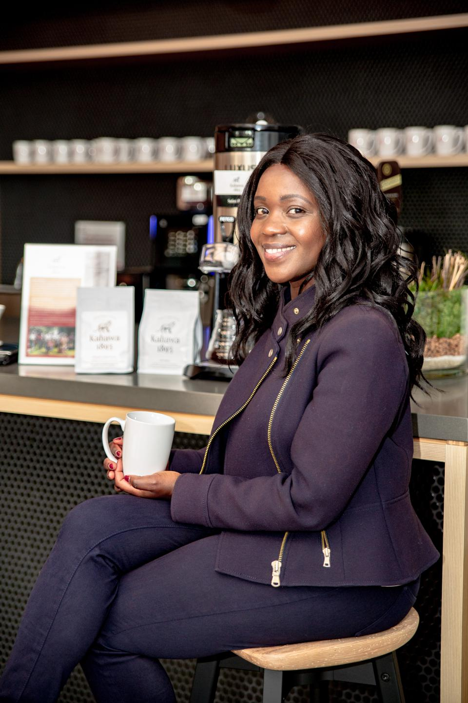 An African woman sits at a counter holding a mug of coffeee.