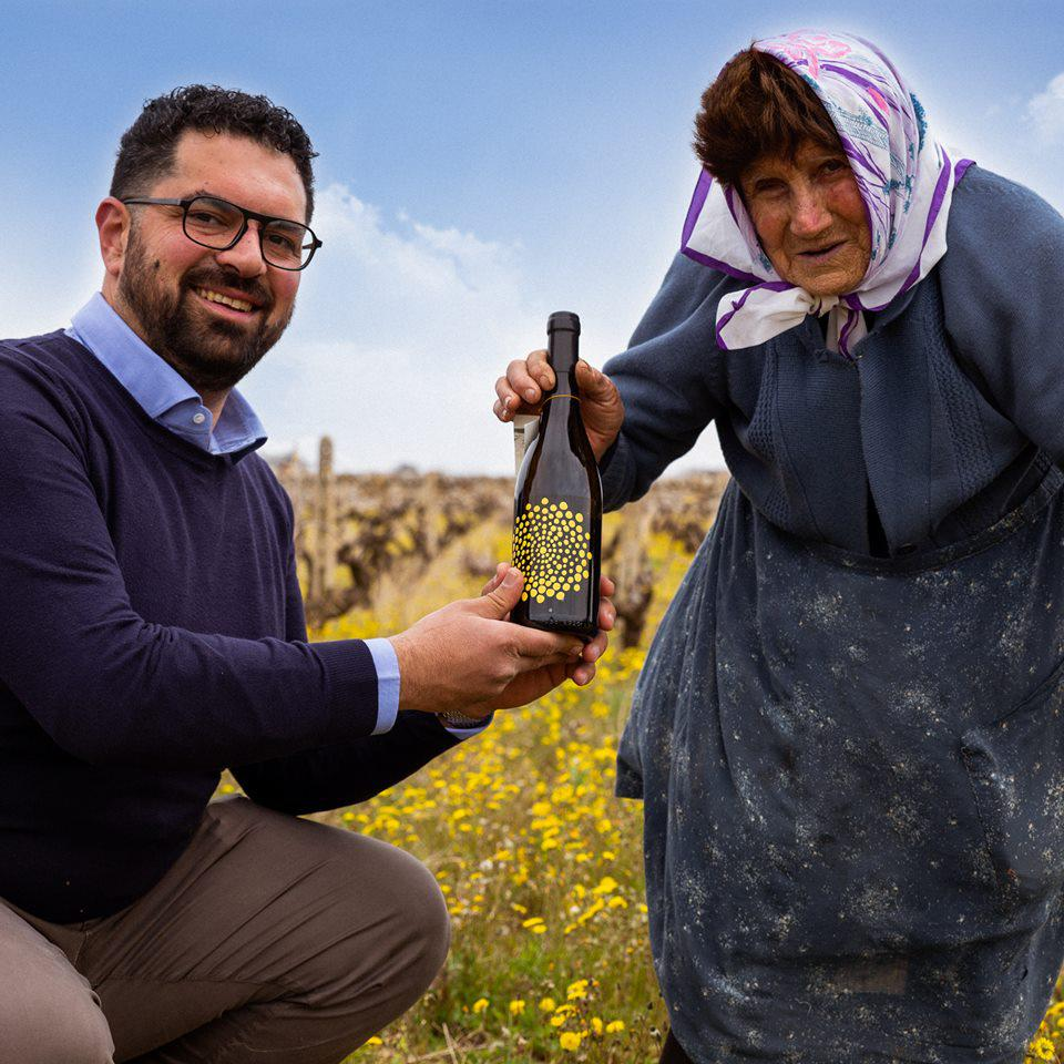 Giovanni and Tonetta in Her Vineyard Holding a Bottle of Essenza