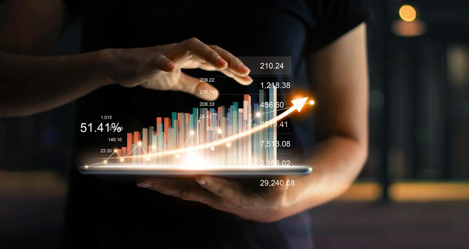 Businessman holding tablet and showing a growing virtual hologram of statistics, graph and chart with arrow up on dark background. Stock market. Business growth, planing and strategy concept.