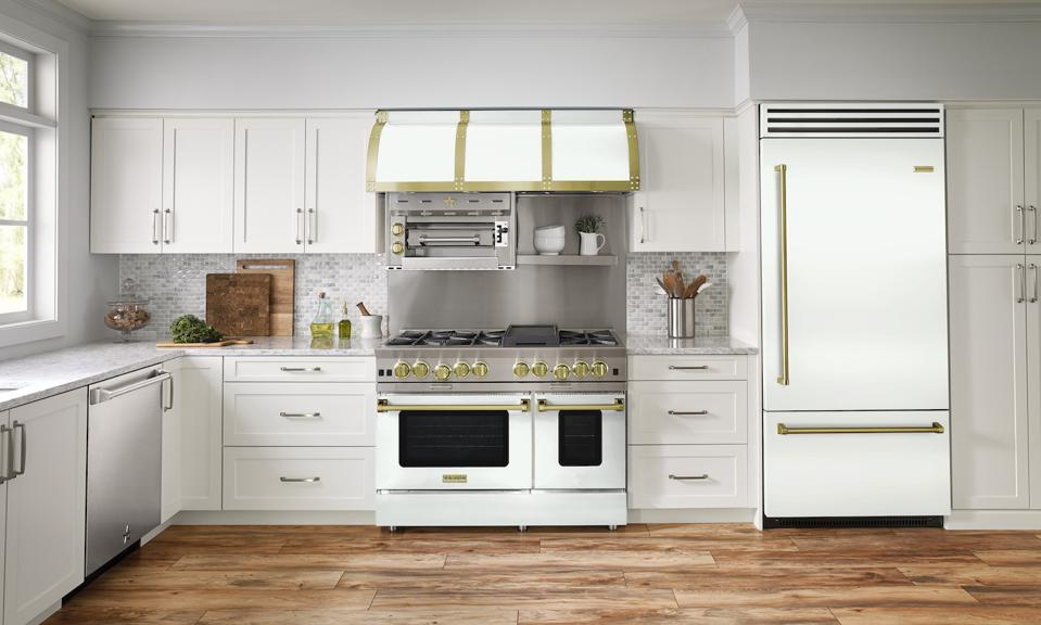 The stove, hood and refrigerator are all BlueStar appliances in white with brass trim and knobs.