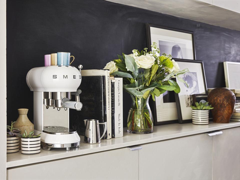 The SMEG White Espresso Machine adds a sculptural element to the white cabinets.