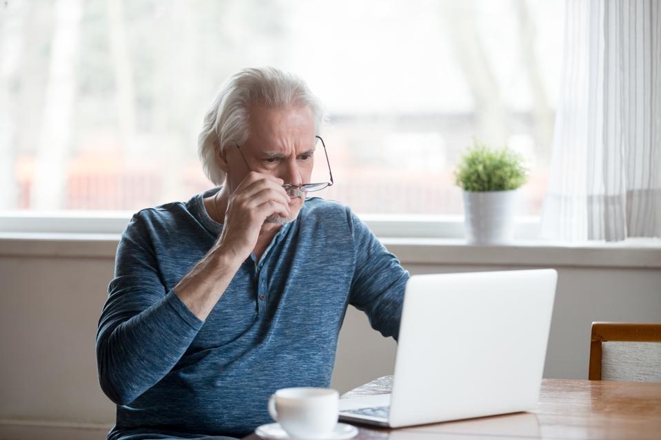 Shocked frustrated senior man taking off glasses looking at laptop