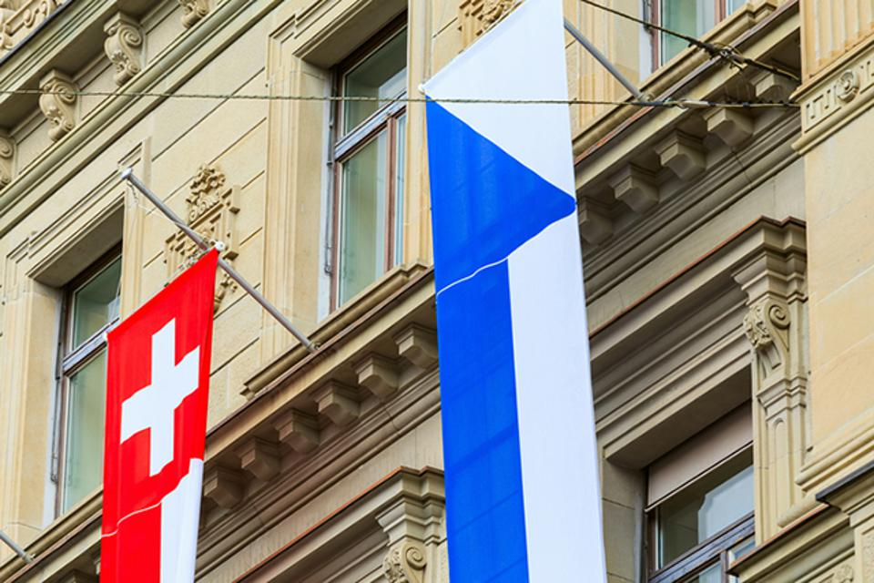 Credit Suisse building at Paradeplatz square in the city of Zurich decorated with flags