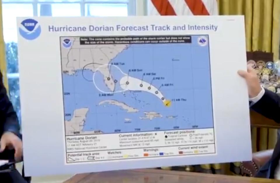 President Trump holds up an altered NHC forecast map.