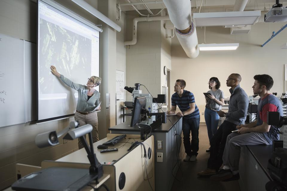 Science professor leading lesson at projection screen classroom