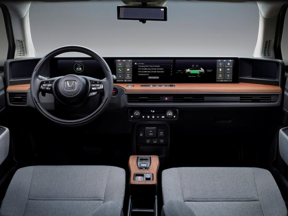 The Honda e interior is a nice mesh of light wood-colored surfaces, LCD panels and a retro-classic steering wheel.