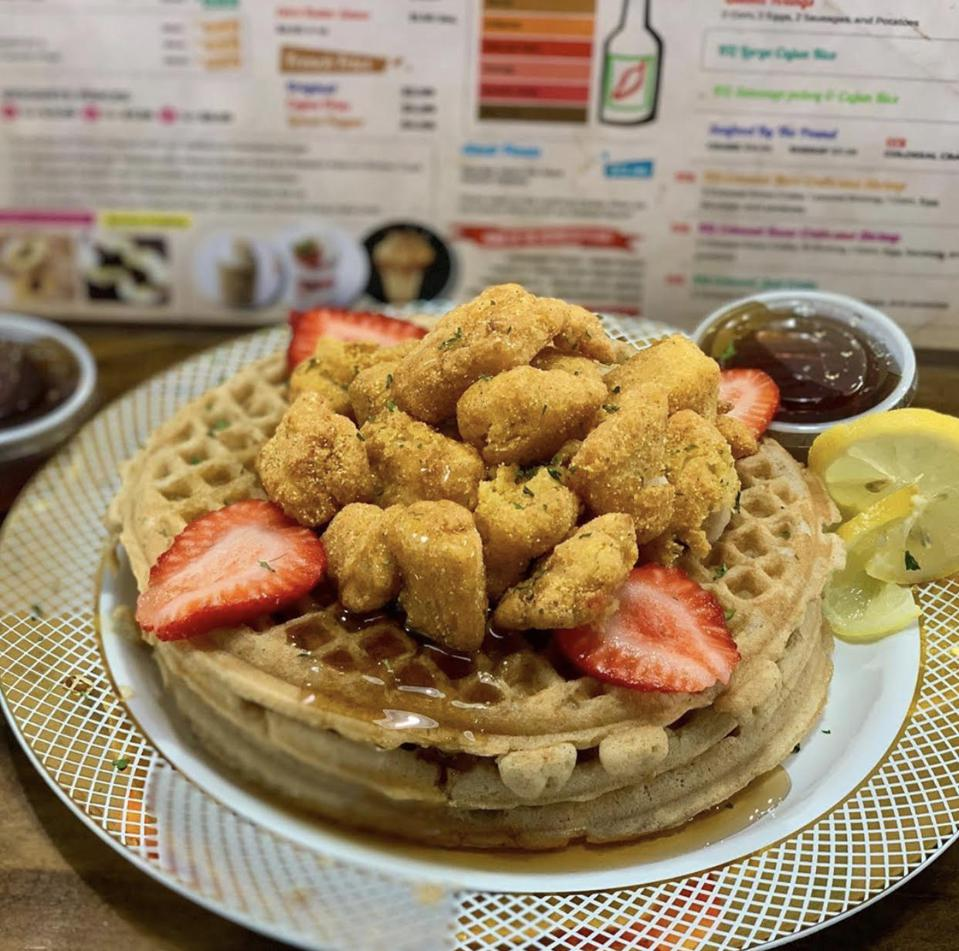 A waffle topped with fried fish and strawberries.