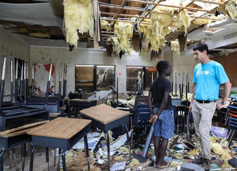 On September 7, 2019, in Marsh Harbour, Abaco Island, Bahamas, 10-year-old Torres talks to UNICEF's Regional Emergency Specialist Hanoch Barlevi in the ruins of his classroom at the Central Abaco Primary School.