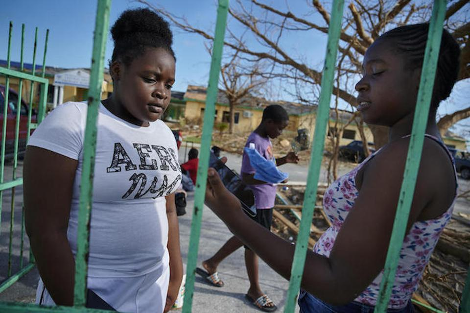 Sixteen-year-old Metory, right, and her 14-year-old sister, Brianna, stand outside the ruins of their school in Marsh Harbour on Abaco Island in the Bahamas.