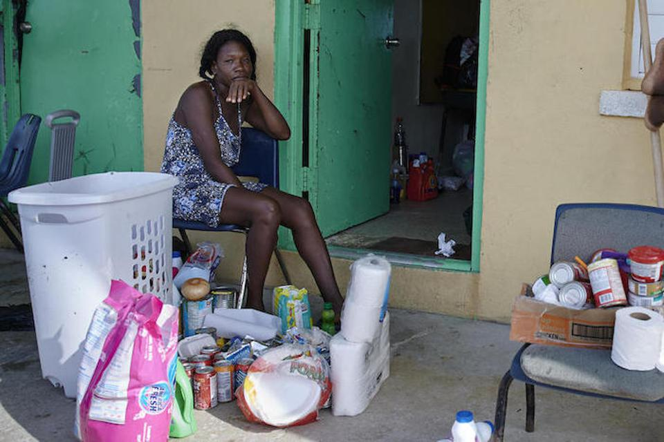 Marie Evelyn, 46, sits outside a classroom at the Central Abaco Primary School where she is living with her children.