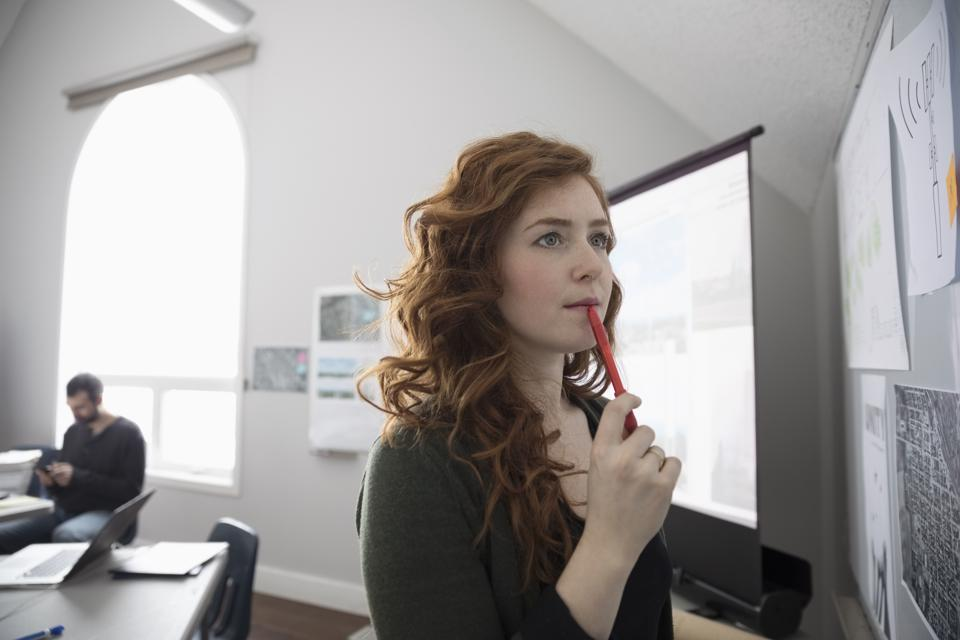 Thoughtful businesswoman brainstorming at whiteboard in office