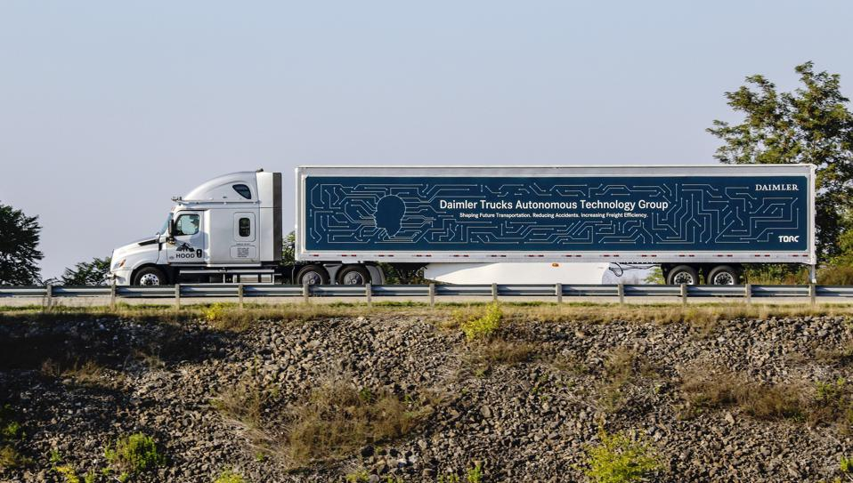 A white and blue semi-truck traveling on the highway.