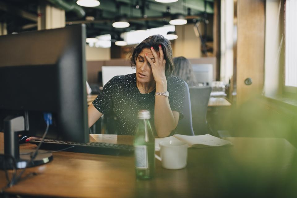 Worried businesswoman with head in hand sitting at computer desk in office