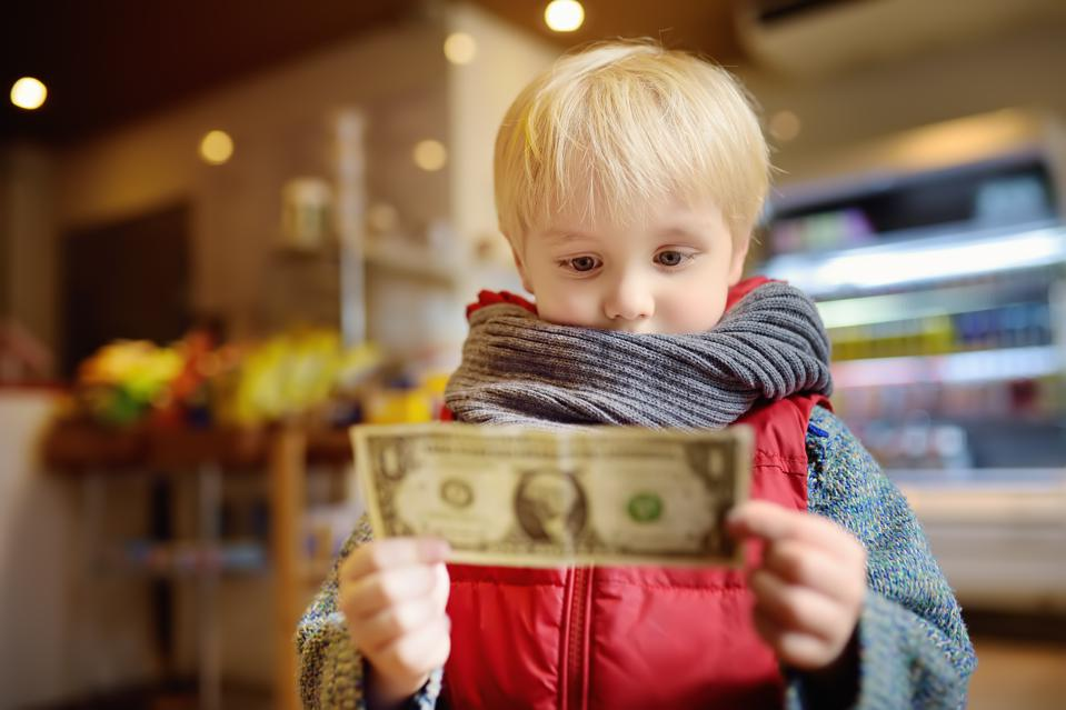 Little boy holds a one-dollar currency note.