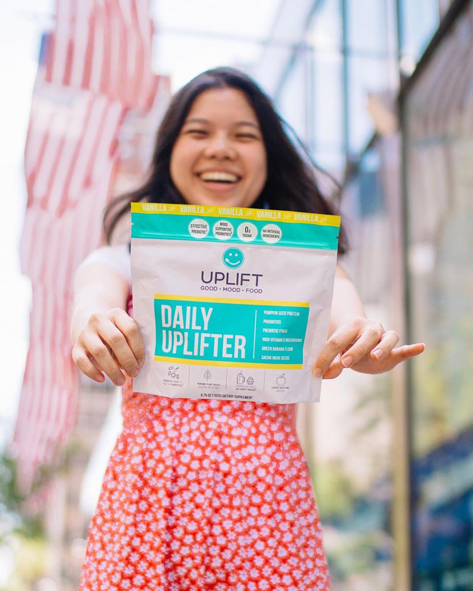 Consumer holding Uplift Food Daily Uplifter