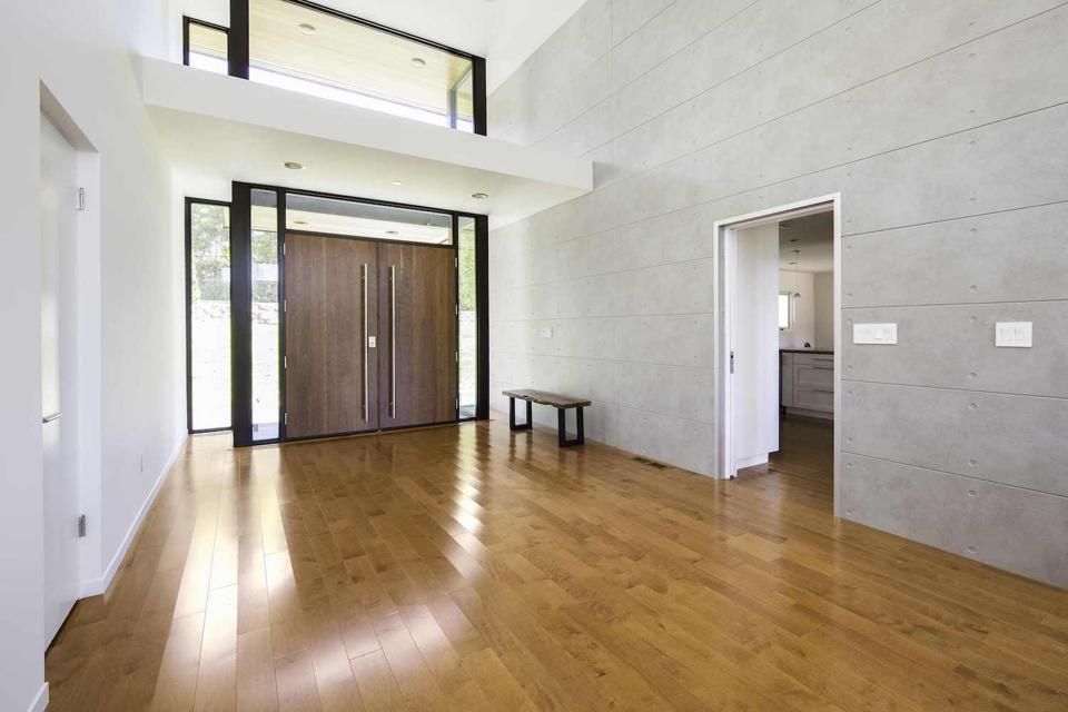 Fiber cement siding used in the interior of the house which is meant to look like a poured concrete wall.