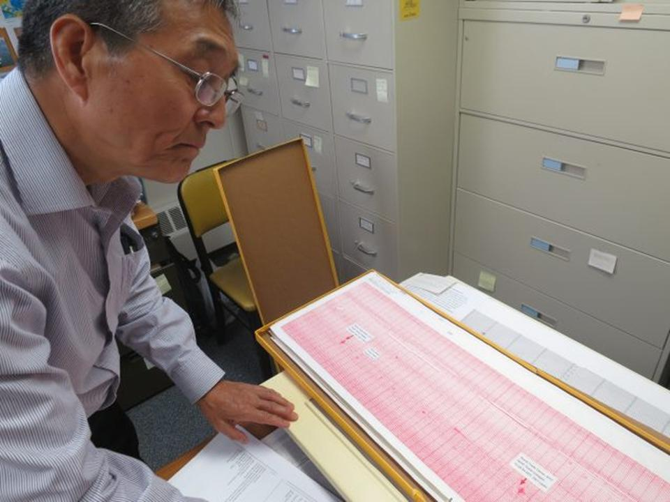 Seismologist Won-Young Kim pulls out the original paper seismogram showing the jet impacts and subsequent collapses of the World Trade Center towers.