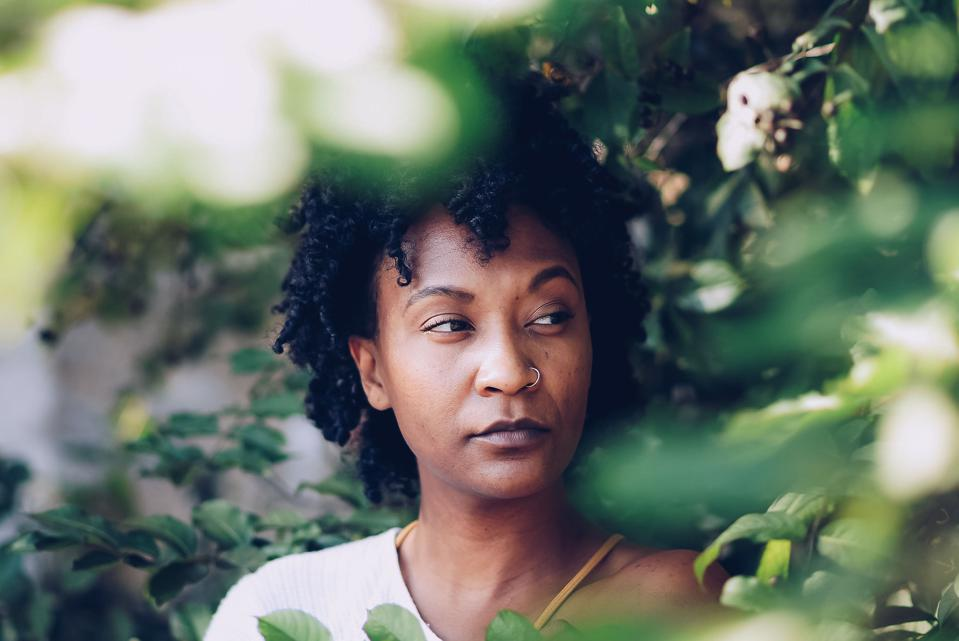A black woman looks reflectively off into the distance.