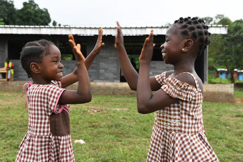 In Sangouine, Côte d'Ivoire, students play happily outside their new classrooms made of recycled plastic bricks through a UNICEF partnership with Conceptos Plasticos, a Colombian company.
