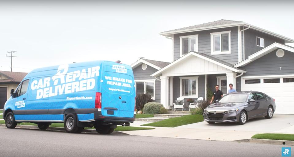 A blue cargo service van parked in front of a house with a car in the driveway.