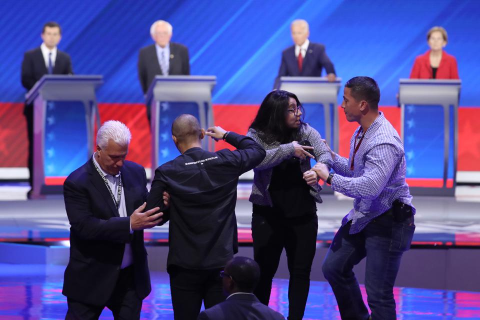 Security guards remove protesters from the debate stage.