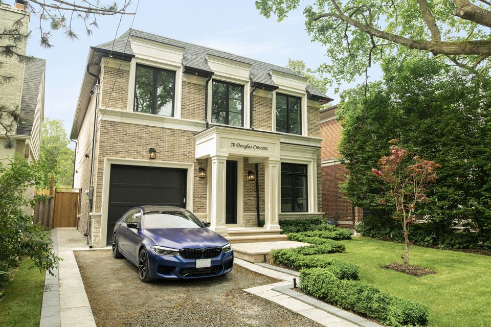 A home staged with a new BMW in the driveway.