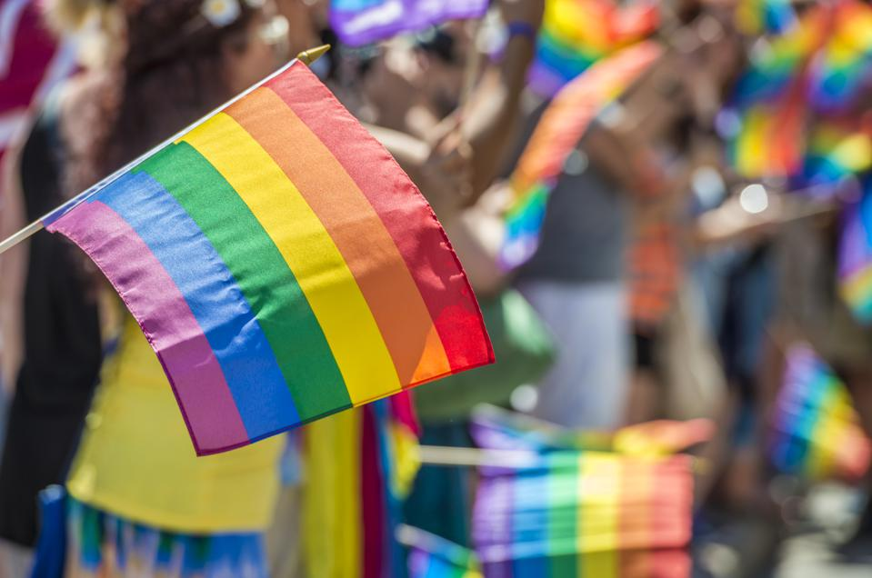 Close-Up Of Rainbow Flag With Crowd In Background During Parade