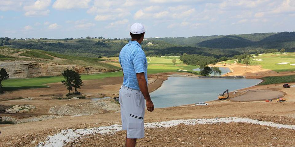 Tiger Woods looks out at his unfinished golf course