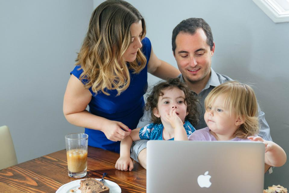 At the kitchen table, Mom looks over Dad' shoulder at a computer, while he holds two young girls in his lap.
