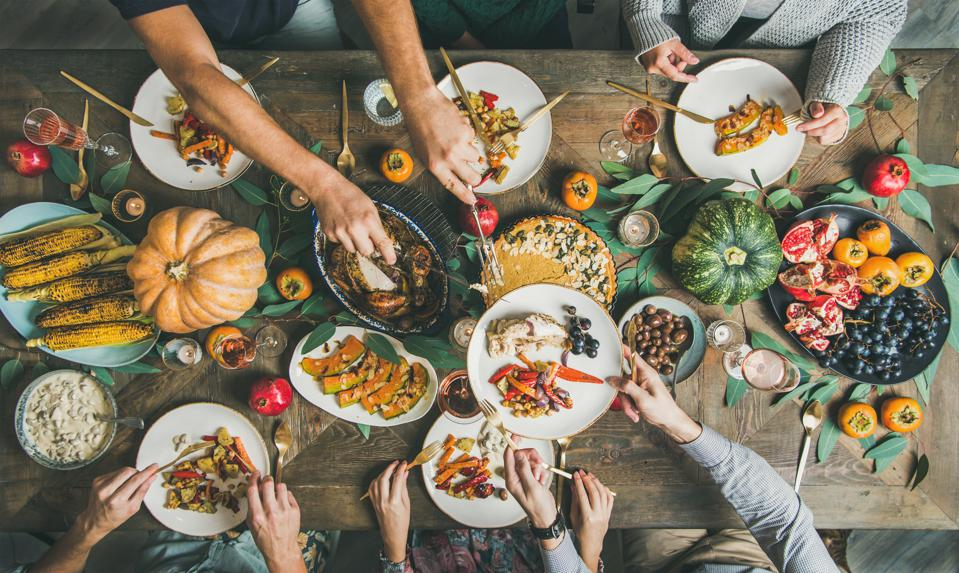 Flat-lay of friends feasting at Thanksgiving Day table with turkey